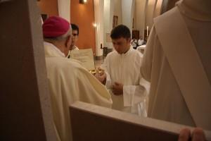 Devid Giovannini riceve da Mons. Crepaldi la patena e le ostie non consacrate